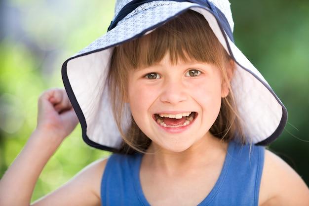 Close-upportret van gelukkig glimlachend meisje in een grote hoed. kind plezier tijd buitenshuis in de zomer.