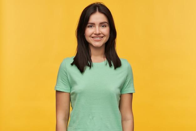 Close-upportret van gelukkige aantrekkelijke donkerbruine jonge vrouw in muntt-shirt die zich over gele muur bevinden glimlacht