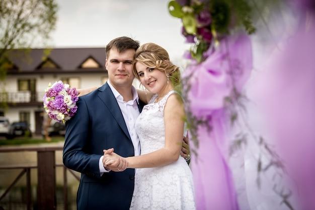 Close-upportret van gelukkige bruid en bruidegom die tegen verfraaide ceremonieplaats bij park koesteren