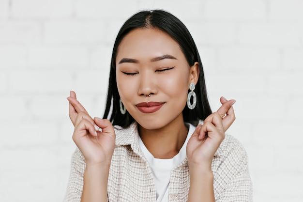 Close-upportret van gelukkige donkerbruine aziatische vrouw in beige jasje glimlacht met gesloten ogen en kruist vingers op witte bakstenen muurmuur