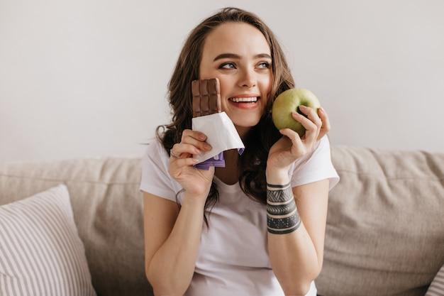 Close-upportret van gelukkige donkerbruine jonge vrouw die groene appel en zoete melkchocolade houdt