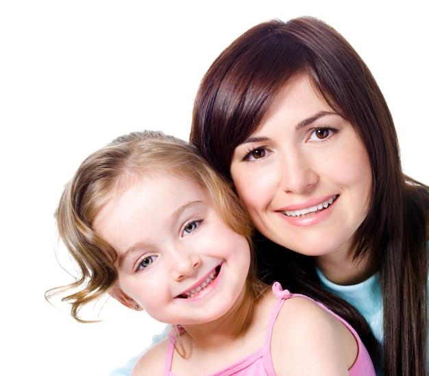Close-upportret van gelukkige het glimlachen gezichten van mooie jonge moeder met dochter