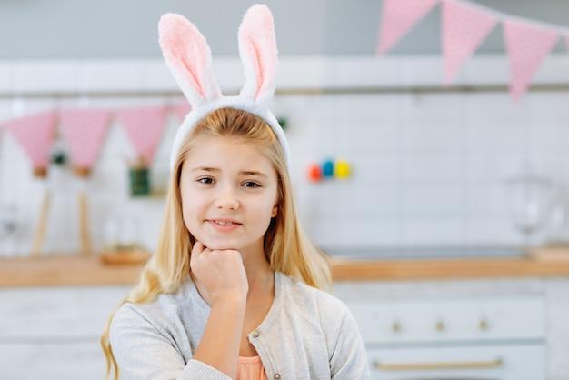 Close-upportret van gelukkige meisjezitting bij de lijst en het dragen van konijntjesoren.
