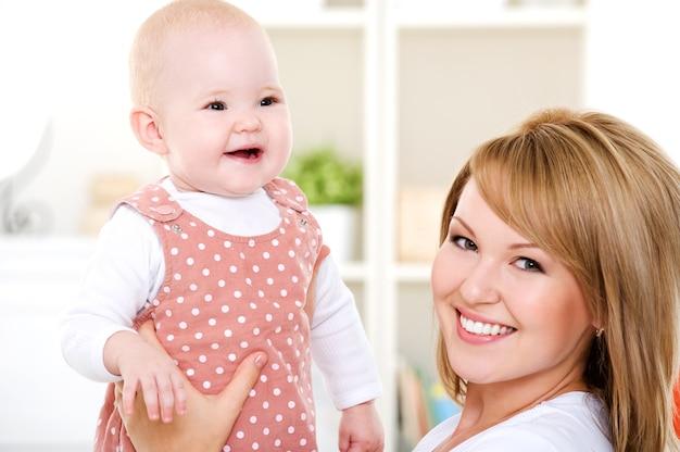 Close-upportret van gelukkige moeder met pasgeboren baby - binnenshuis