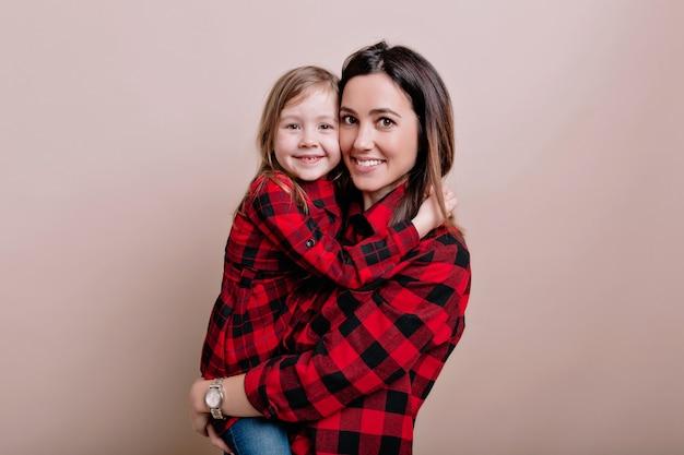 Close-upportret van gelukkige vrouw met klein schattig meisje die gelijkaardige gecontroleerde overhemden dragen glimlachen en plezier hebben, mooi familieportret, ware emoties, geïsoleerde muur, plaats voor tekst