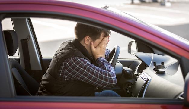 Close-upportret van geschokt mannelijk bestuurder sluitend gezicht met handen