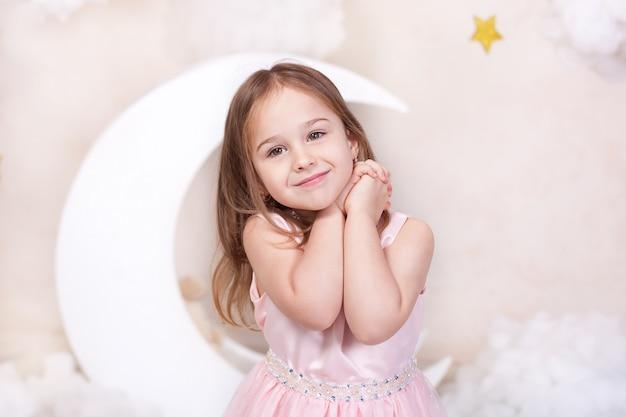 Close-upportret van gezicht van meisje met lang haar. mooi meisje op een muur van maan, sterren en wolken. kind droomt. kind is blij. schattig klein meisje glimlachen. concept jeugd