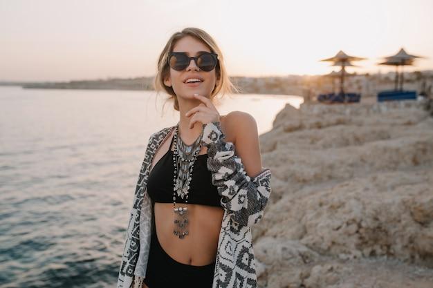 Close-upportret van glimlachend jong meisje op strand, zonsondergangtijd. trendy zwart zwempak, bikini, stijlvolle zonnebril, ketting, vest, cape met ornamenten.