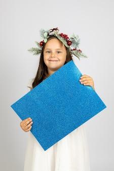 Close-upportret van glimlachend prachtig meisje in kerstboomkroon die blauwe zilveren glanzende lege ...