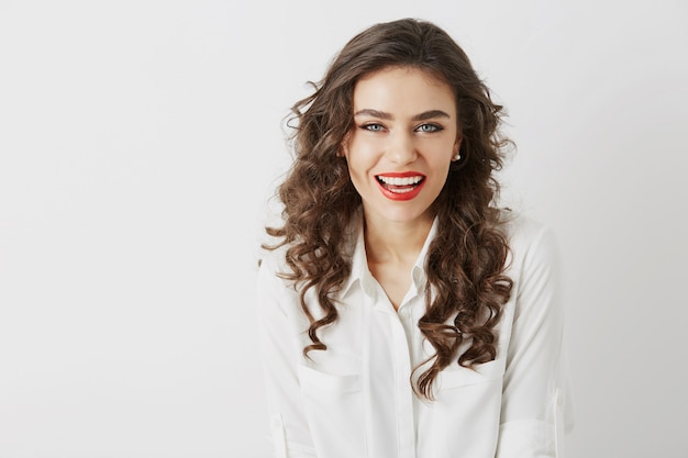Close-upportret van glimlachende aantrekkelijke vrouw met witte tanden, lang krullend haar, rode geïsoleerde lippenstiftsamenstelling die witte blouse draagt