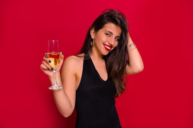 Close-upportret van glimlachende gelukkige vrouw met lang donker haar die met een glas champagne stellen over geïsoleerde rode achtergrond