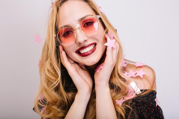 Close-upportret van glimlachende jonge blonde in roze glazen, partijfotoshoot, overal confetti. heeft een mooie glimlach, lang krullend haar, ziet er cool uit in een zwarte jurk.