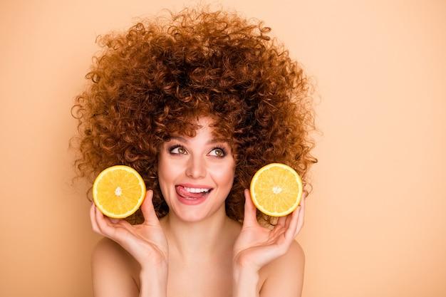 Close-upportret van golvend-haired meisje in handen houden oranje halve tong uitsteekt