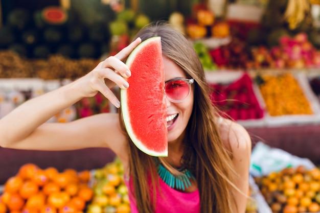 Close-upportret van grappig meisje in roze zonnebril die plak van watermeloen op half gezicht op tropische vruchtenmarkt houden