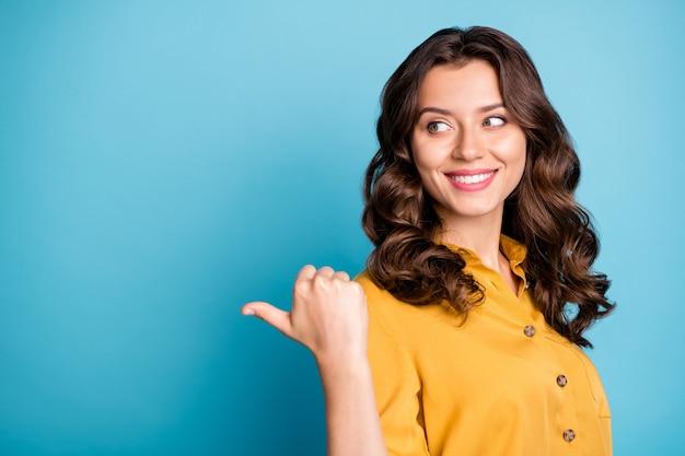 Close-upportret van haar dat zij aardig aantrekkelijk charmant zelfverzekerd vrolijk vrolijk golvend-haired meisje duim opzij advertentie toont.