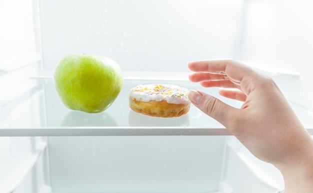 Close-upportret van hand die tussen appel en doughnut bij koelkast kiest