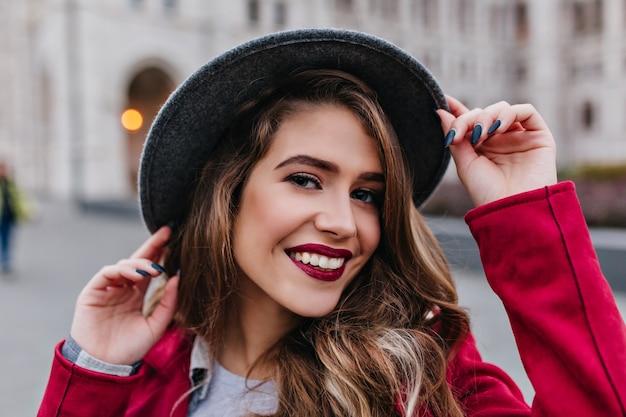 Close-upportret van het koelen jonge vrouw met het rode lippen speels glimlachen