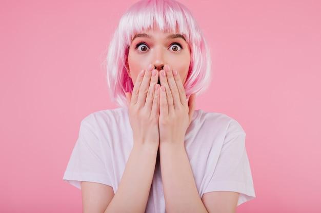 Close-upportret van het leuke geschokte jonge vrouw stellen in roze peruke. binnen schot van bang meisje in periwig geïsoleerd op pastel muur