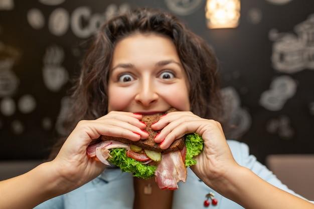 Close-upportret van hongerige jonge kaukasische vrouw, bijtsandwich