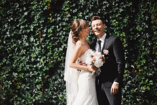 Close-upportret van huwelijksbruid en bruidegom met boeket het stellen. bruidspaar, gelukkige jonggehuwde vrouw en man knuffelen. bruid en bruidegom
