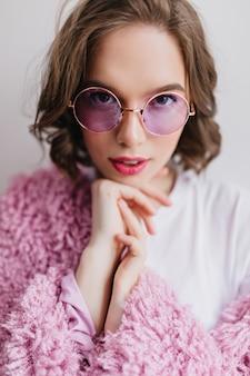Close-upportret van innemend donkerogig meisje in roze jasje. prachtig vrouwelijk model in pluizige jas geïsoleerd op een witte muur.