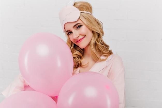 Close-upportret van innemend feestvarken dat van ochtend geniet. mooie glimlachende vrouw die in oogmasker iets met ballons viert.