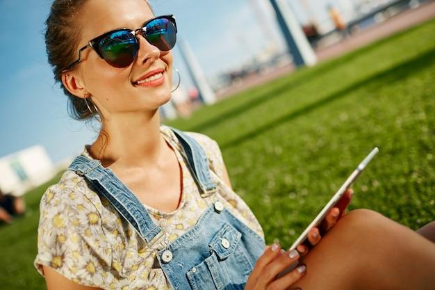 Close-upportret van jong blondemeisje met koffie en tablet