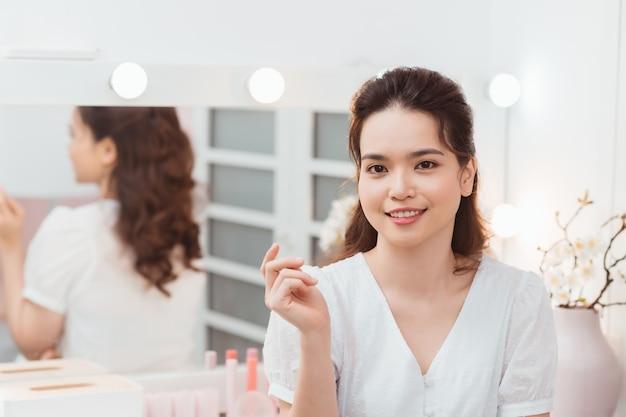 Close-upportret van jong mooi aziatisch meisje met spiegel voor make-uproutine met exemplaarruimte.