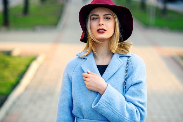 Close-upportret van jong mooi glimlachend meisje in een blauwe laag en de hoed die van bourgondië onderaan de straat op een zonnige de lentedag lopen