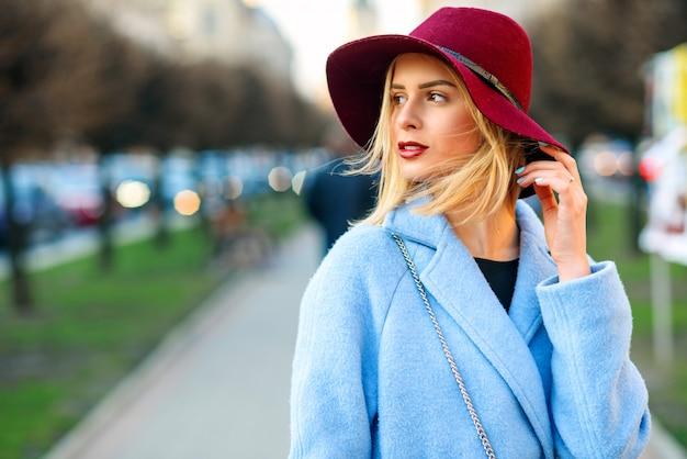 Close-upportret van jong mooi meisje in een blauwe laag en een bourgondische hoed die onderaan de straat op een zonnige de lentedag lopen