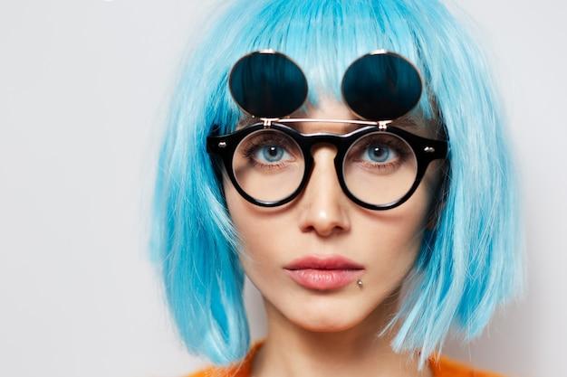 Close-upportret van jong mooi meisje met blauw haar en ronde tinten.
