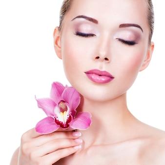 Close-upportret van jong mooi meisje met bloem dichtbij het gezicht - dat op witte achtergrond wordt geïsoleerd