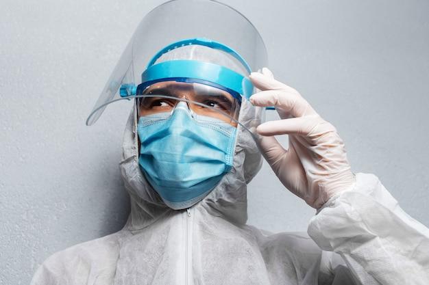 Close-upportret van jonge arts die ppe-kostuum draagt tegen coronavirus en covid-19, op achtergrond van grijze muur.