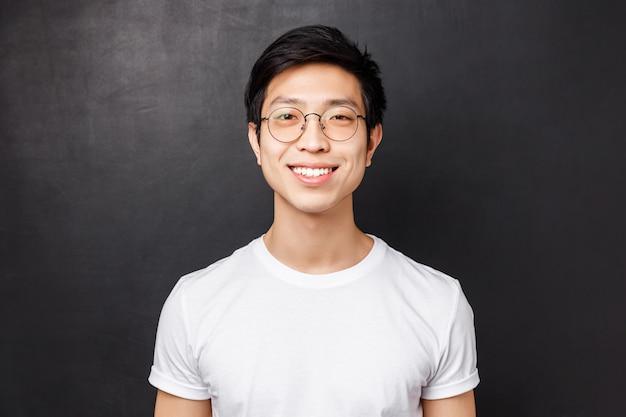 Close-upportret van jonge aziatische kerel in glazen en eenvoudig wit t-shirt, bekijkend camera met tevreden vriendelijke uitdrukking, stralende glimlach, blogger sprekend aan publiek hoe aanwinst volgers