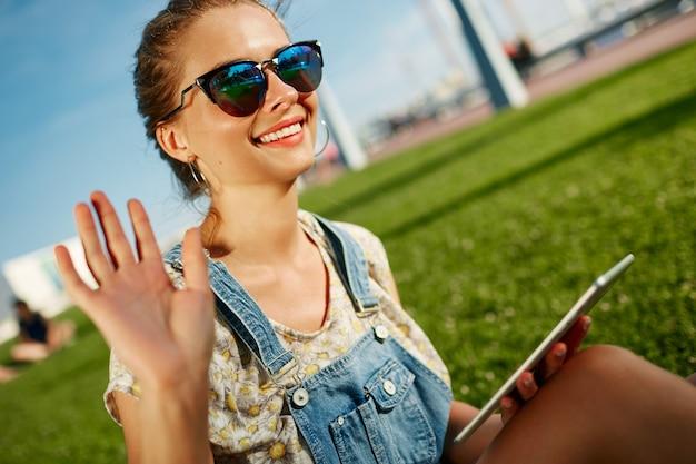 Close-upportret van jonge blonde vrouw met tablet