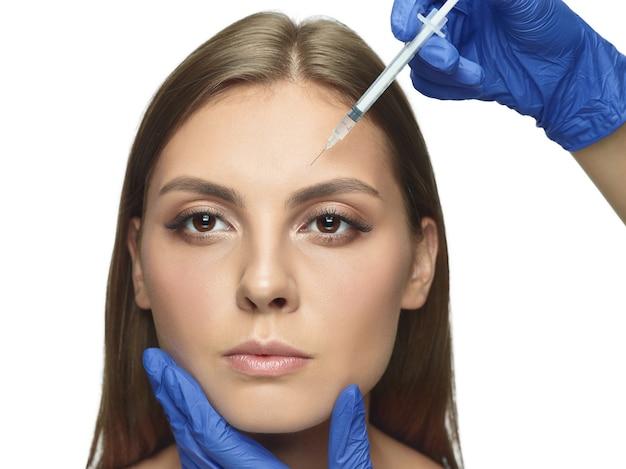 Close-upportret van jonge die vrouw op witte studiomuur wordt geïsoleerd bij het vullen van chirurgieprocedure