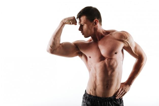 Close-upportret van jonge half naakte bodybuilder die zijn bicepsen bekijken
