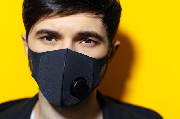 Close-upportret van jonge kerel die ademhalingsgezichtsmasker van zwarte kleur draagt, tegen coronavirus. achtergrond van gele kleur.
