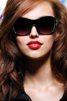 Close-upportret van jonge maniervrouw met glamourzonnebril
