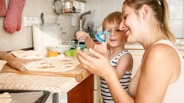 Close-upportret van jonge moeder die haar peuterzoon onderwijzen die koekjes maakt. kind met ouder die desserts bakt op bakpan bij keuken in huis