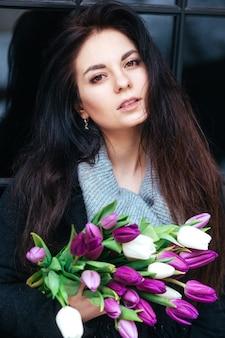 Close-upportret van jonge mooie donkerbruine vrouw met tulpen