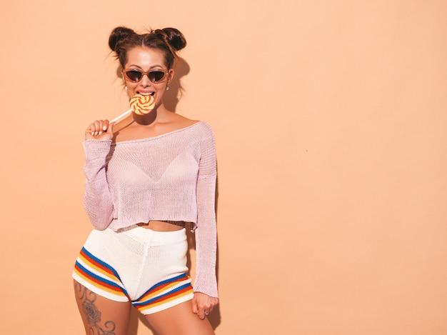 Close-upportret van jonge mooie sexy glimlachende vrouw met lijkenetende kapsel. trendy meisje in casual zomer kleding in zonnebril. heet model geïsoleerd op beige. eten, bijten snoep lolly