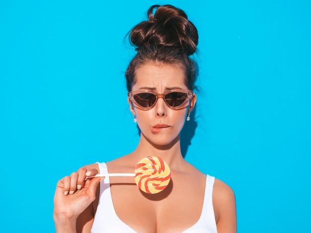 Close-upportret van jonge mooie sexy vrouw met lijkenetende kapsel. trendy meisje in casual zomer wit zwempak in zonnebril. heet model geïsoleerd op blauw. eten, bijten snoep lolly