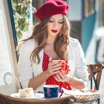 Close-upportret van jonge mooie vrouw die rode baret draagt.