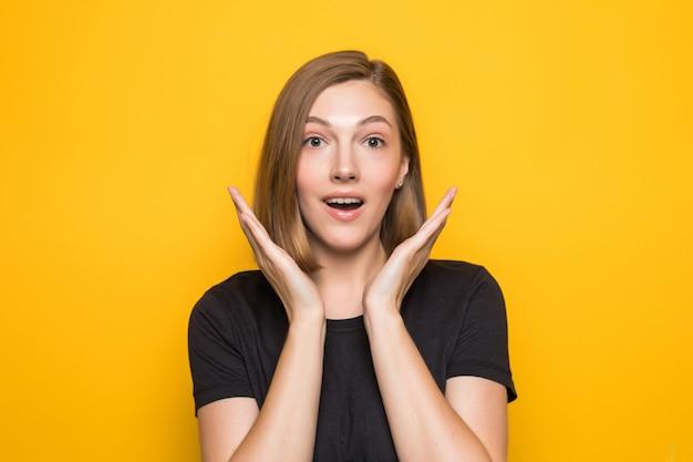Close-upportret van jonge vrij verraste vrouw met geopende mond die zich met open handpalmen bevindt