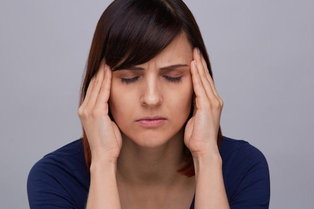 Close-upportret van jonge vrouw die aan sterke hoofdpijn lijden, vingers aan tempels houden en ogen sluiten van pijn. ernstige migraine.