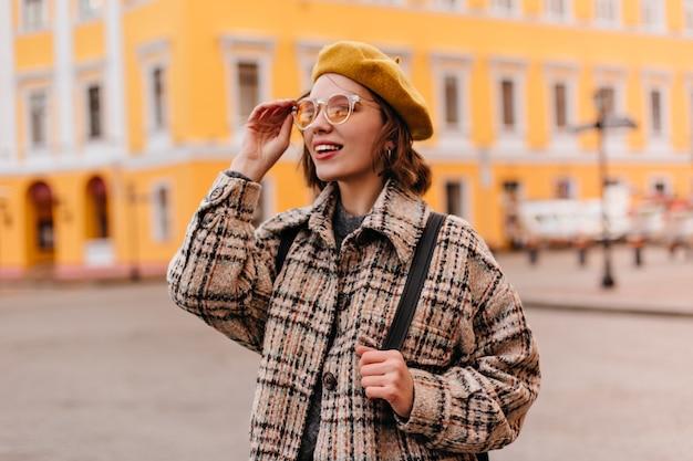 Close-upportret van jonge vrouw die in zonnebril stadsgezicht bewonderen