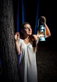 Close-upportret van jonge vrouw die 's nachts in het bos verdwaald is