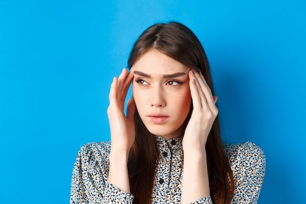 Close-upportret van jonge vrouw die zich ziek voelt, hoofdtempels aanraakt en fronst van hoofdpijn, migraine heeft, opzij kijkt naar logo, blauw.