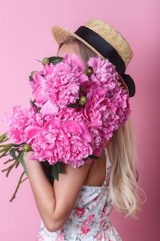 Close-upportret van jonge vrouw in de zomerkleding en het boeket van strohoedholding pioenen over haar schouder